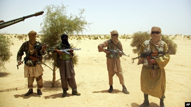 Ansar Dine Islamist fighters stand guard during a hostage handover in the desert outside Timbuktu, Mali, April 24, 2012.