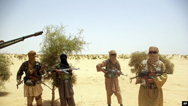 An April 24, 2012 photo shows Ansar Dine Islamist fighters standing guard during a hostage handover in the desert outside Timbuktu, Mali.
