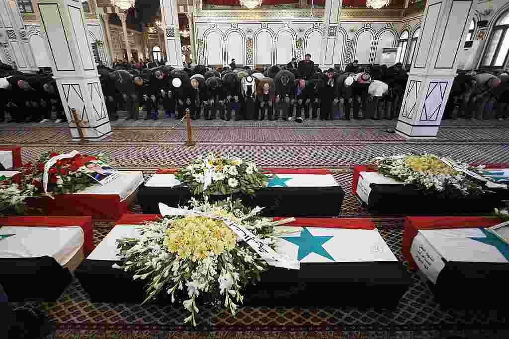 Para pelayat melakukan sholat jenazah pada pemakaman para korban ledakan di Damaskus (AP).