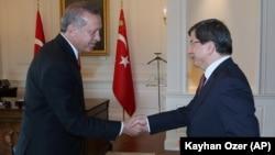 FILE - Turkish President Recep Tayyip Erdogan, left, and Prime Minister Ahmet Davutoglu shake hands, in Ankara, Turkey.