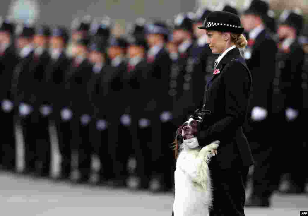 A police officer and her police dog stand at attention at the Metropolitan Police parade to mark the graduation of 182 new recruits from the Metropolitan Police Academy, at Hendon, northwest London.