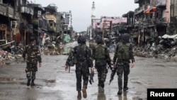 Government troops pass destroyed buildings and houses in Datu Sa Dansalan in Marawi city, southern Philippines, Oct. 17, 2017.
