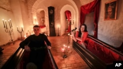 Tami Varma (R) and her brother Robin, grandchildren of an expert in vampire lore, pose in coffins at Dracula's Castle, in Bran, Romania, Oct. 31, 2016. The pair bested 88,000 people in a competition to win the chance of a night at the famed landmark.