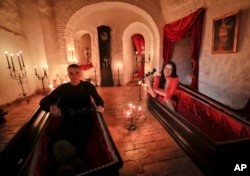 These two fans of vampire folklore pose in coffins at Dracula's Castle in Romania, 2016.