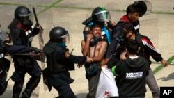 泰國一名反政府抗議者(中)在曼谷體育館發生衝突時被警察驅逐。(2013年12月26日照片)