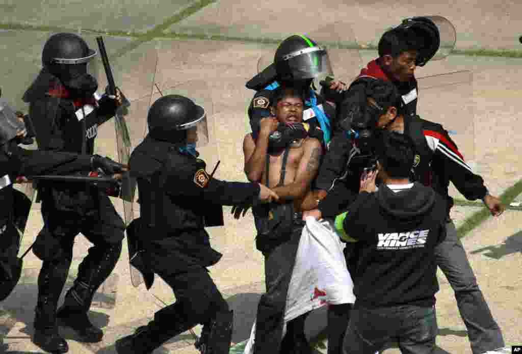 An anti-government protester is detained by riot police during a clash at a sports stadium in Bangkok, Thailand. Rock-throwing protesters trying to halt preparations for elections fought police in the capital, escalating their campaign to topple the country's beleaguered government.