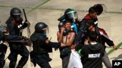Cảnh sát Thái Lan bắt một người biểu tình phản đối chính phủ tại một sân vận động, 26/12/13