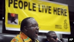 Amnesty International 's Kenya director, Justus Nyang'aya gestures as he addresses the media in Nairobi on forced evictions of people from urban slums across Africa, March 22, 2012.