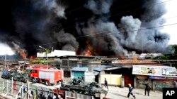 Para petugas pemadam kebakaran berupaya memadamkan api yang menghancurkan rumah-rumah penduduk, sementara tentara pemerintah terus memerangi pemberontak muslim di kawasan Zamboanga, Filipina selatan (12/9).