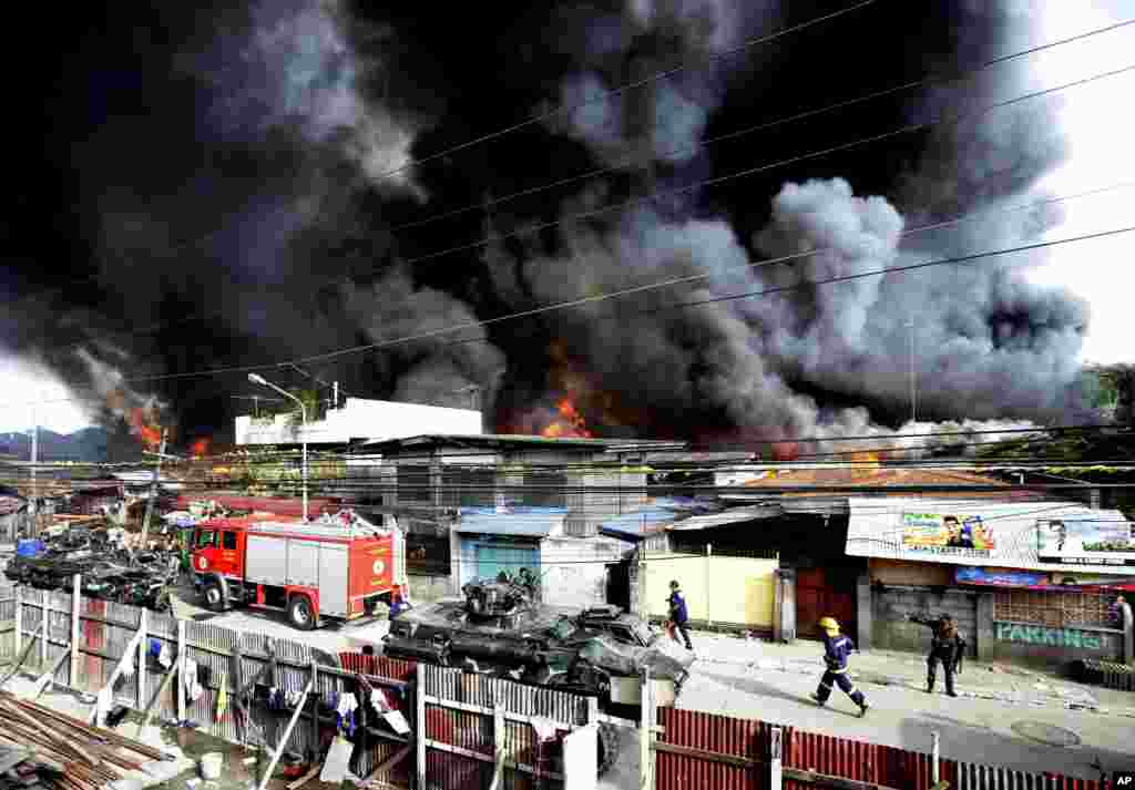 Firemen rush to put out a fire that razed several homes as government troopers continue their assault on Muslim rebels in Zamboanga, Philippines, Sept. 12, 2013.