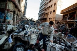 An Egyptian man makes his way through rubble at the scene of an explosion at a police headquarters building in the Nile Delta city of Mansoura, Egypt, Dec. 24, 2013.