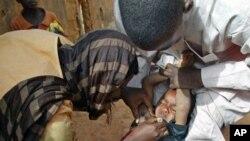 Volunteers administer polio vaccine to a child in Kaduna, Nigeria, (File)