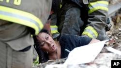 2013年5月20日美国中部的俄克拉荷马州遭到龙卷风袭击,俄克拉荷马市郊摩尔社区的一所学校被摧毁,救援人员在瓦砾中营救一名妇女。