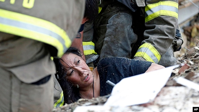 A woman is pulled out from under tornado debris at the Plaza Towers School in Moore, Oklahoma, May 20, 2013.