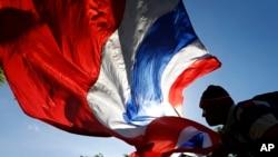 Seorang pengunjuk rasa anti-pemerintah melambaikan bendera nasional Thailand ketika terjadi unjuk rasa di Bangkok. Komisi anti korupsi negara itu mendakwa perdana menteri yang digulingkan Yingluck Shinawatra atas tuduhan kelalaian dalam tugas mengawasi program subsidi beras yang mendapat kecaman luas.