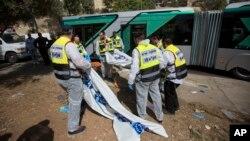 Petugas Israel mengangkut korban serangan di sebuah bus di Yerusalem, Selasa (13/10).