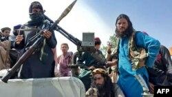 صوبہ لغمان کی ایک سڑک پر طالبان جنگجو ایک گاڑی میں سوار۔ 15 اگست، 2021ء