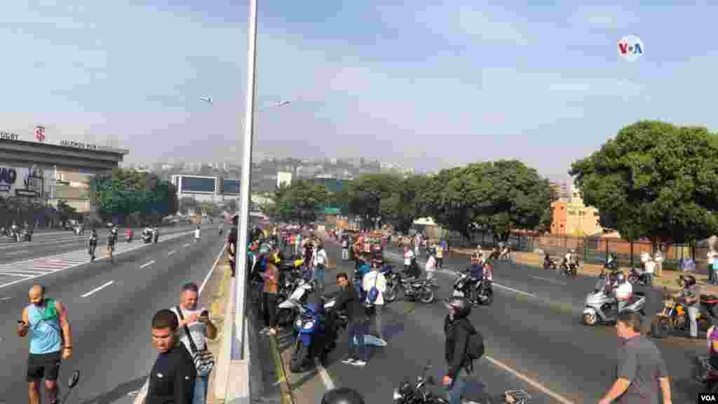 """El presidente encargado de Venezuela, Juan Guaidó, convocó el martes desde una importante base aérea de Caracas a soldados y civiles a salir a las calles para buscar """"el cese definitivo"""" del gobierno en disputa del país."""