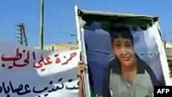An image grab taken from YouTube on May 28, 2011, shows a Syrian man holding a picture of 13-year-old boy Hamza al-Khatib during his funeral on May 25, 2011 in the flashpoint region of Daraa, Syria.
