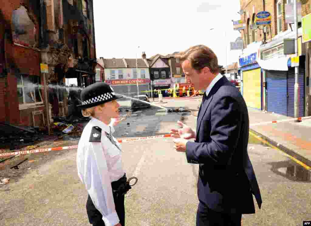 9 tháng 8: Thủ tướng Anh David Cameron nói chuyện với bà Jo Oakley, quyền quận trưởng cảnh sát của một quận bị đốt phá ở phía nam London. REUTERS/Stefan Rousseau