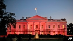 The White House in Washington is bathed in pink light to celebrate Breast Cancer Awareness Month.