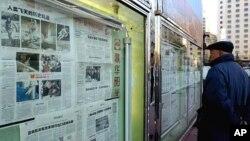 중국 베이징 거리에 진열된 신문을 들여다 보는 시민. (자료사진)