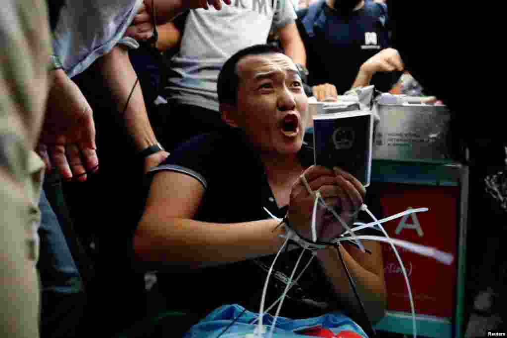 Fu Guohao, a reporter of Chinese media Global Times website, is tied by protesters during a mass demonstration at the Hong Kong international airport, in Hong Kong.
