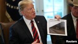 """Президент США Дональд Трамп с фотографией """"Типичной стандартной конструкции стены"""" на границе (архивное фото)"""
