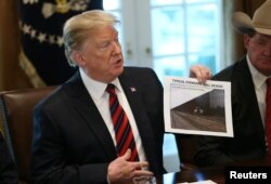 "FILE - President Donald Trump holds up a photo of a ""Typical Standard Wall Design"" as he hosts a discussion on border security and safe communities with state, local, and community leaders in the Cabinet Room of the White House in Washington, Jan. 11, 2019."