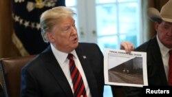特朗普總統舉著一張邊境牆的照片。(資料圖片)