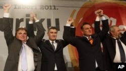 Opposition leader Zoran Milanovic, center left, surrounded by his coalition partners Ivan Jakovic, left, Radomir Cacic, center right and Silvano Hrelja celebrate at their party headquarters in Zagreb, Croatia, December 4, 2011.