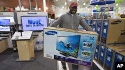 """美國感恩節過後的一天被稱做""""黑色星期五""""﹐一名顧客在Bestbuy商店購買電視後﹐笑容滿面離開。"""