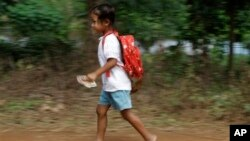 A Cambodian school girl runs home after her morning primary school in Rokar Tnong village on the outskirts of Phnom Penh, Cambodia, Thursday, Oct. 6, 2011. (AP Photo/Heng Sinith)