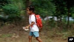 Một học sinh Campuchia trong vùng ngoại ô Phnom Penh chạy vội về nhà sau buổi học,