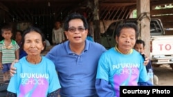 Im Chaem and her husband are pictured with pastor Christopher LaPel, middle, outside of her home in O'Angre village, Anlong Veng district, Oddar Meanchey province, Cambodia. (Courtesy photo of Pastor Touch Chanthou)