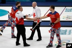 Norway's Christoffer Svae, right, shakes hands with Canada's Ben Herbert after their match at the 2018 Winter Olympics in Gangneung, South Korea, Feb. 15, 2018. At the Pyeongchang Olympics, curlers and their fans agree: In an era of vitriol and venom, curling may be the perfect antidote to our troubled times.