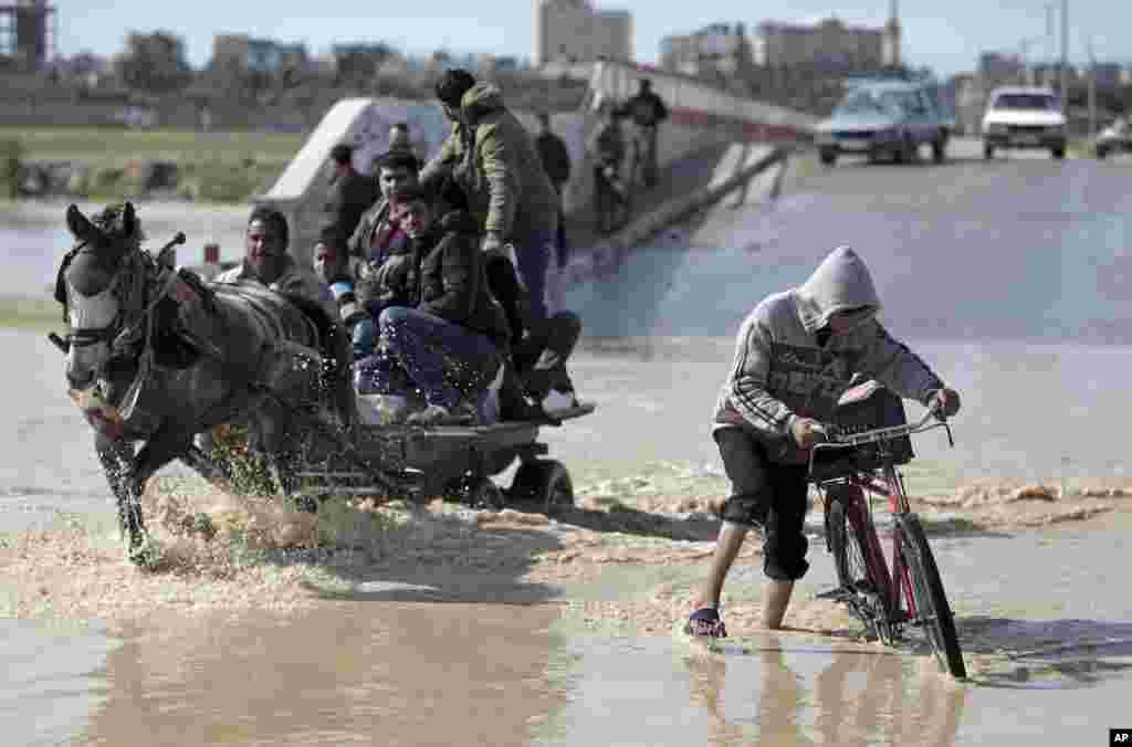 Warga Palestina menyeberangi jalan yang banjir di desa Bedouin, al-Moghraka, Jalur Gaza tengah.