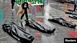 Pengunjuk rasa di Manhattan, New York, beraksi menggunakan kantong jenazah yang mewakili korban tewas corona, 1 Mei 2020. (Foto: Reuters)