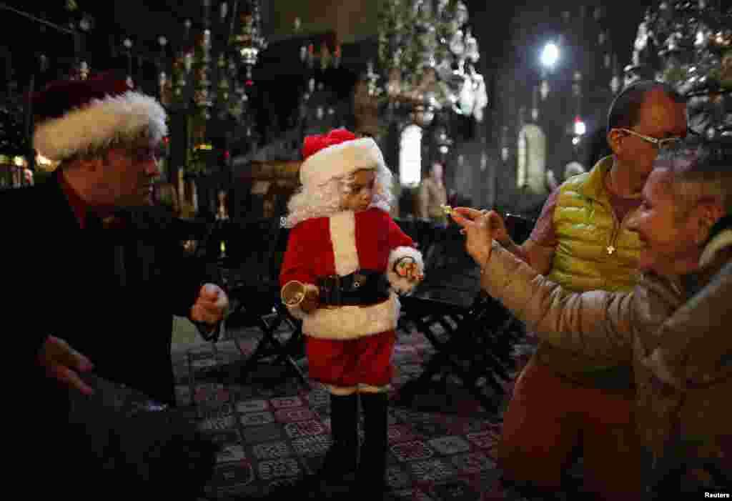 Мальчик в костюме Санта-Клауса в церкви Рождества Христова. Вифлеем