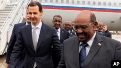 Presiden Suriah Bashar al-Assad (kiri) menerima kunjungan Presiden Omar al-Bashir di Damaskus, Minggu (16/12).