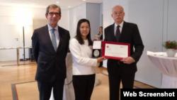 北京人权律师余文生的妻子许艳在领奖后与德法两国大使合影。(推特截图)