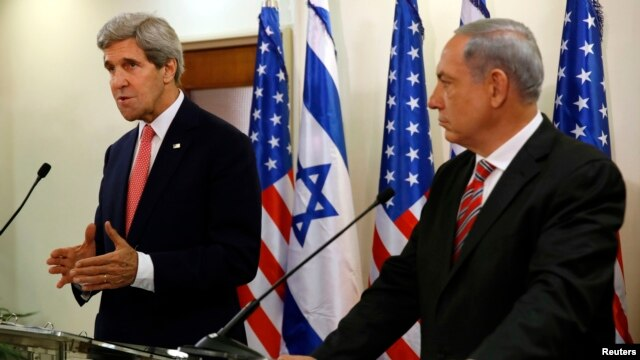 Israeli Prime Minister Benjamin Netanyahu (R) listens as U.S. Secretary of State John Kerry speaks during a news conference following a meeting at Netanyahu's office in Jerusalem, Dec. 5, 2013.