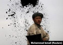 Seorang buruh tambang batubara membongkar muatan batubara dari truk ke tempat penimbunan di Kabul, Afghanistan,19 November 2015. (Foto:Reuters).