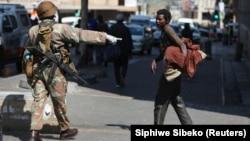 Un membre des Forces de défense nationale sud-africaines demande à un sans-abri de déguerpir, à Johannesburg, Afrique du Sud, le 27 mars 2020. (Photo: REUTERS/Siphiwe Sibeko)