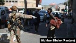 Un militaire sud-africain s'adresse à un sans-abri lors du premier jour d'un confinement national de 21 jours pour tenter de contenir l'épidémie de coronavirus, à Johannesburg, Afrique du Sud, le 27 mars 2020. (Photo: Siphiwe Sibeko/Reuters)