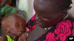 In this photo taken from Video provided by Associated Press on Tuesday, May 13, 2014, a malnourished child is fed by her mother, in a Medecins Sans Frontiers (Doctors Without Borders) hospital, in Leer, South Sudan. Bodies stuffed in wells. Houses burn