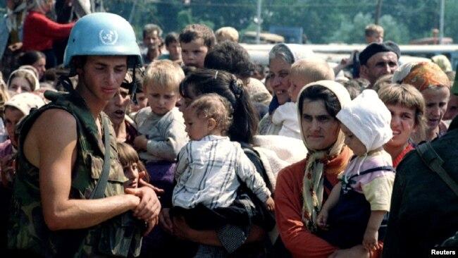 Žene i deca, uz pripadnika holandskog bataljona UN, čekaju na transportovanje iz Potočara; 12. jul 1995.