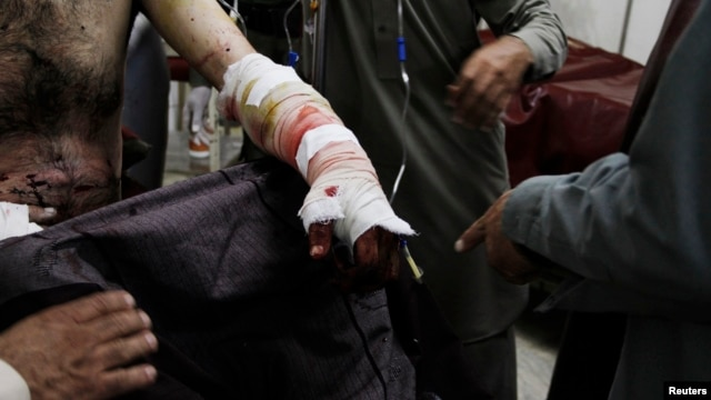 A man injured in a bomb blast during an election campaign rally of the Jamiat Ulema-e-Islam religious party at Kurram agency, sits at a hospital in Peshawar May 6, 2013.