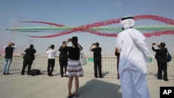 Para turis menyaksikan akrobatik udara pada pameran kedirgantaran Dubai (Dubai Airshow) di Dubai, Uni Emirat Arab, Minggu (8/11).