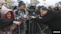 Позафракційнийдепутат Петро Порошенко розмовляє з дитиною під час Народного віче на Майдані Незалежності в Києві, 12 січня 2014 року